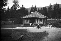 Framför ett bostadshus (?) sitter några vuxna och två pojkar