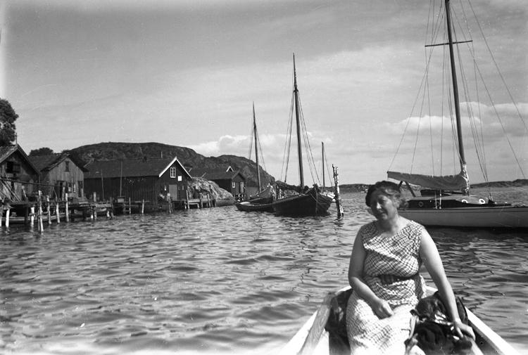 En kvinna sitter i en båt.Bakom henne syns en hamn med några bodar och brygga.