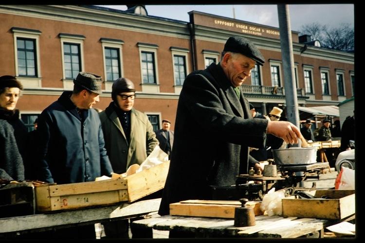 Fiskförsäljning på torget i Växjö. Vid ett marknadsstånd står en man och väger fiskfiléer. I bakgrunden syns Residenset.