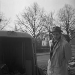 Närbild av en man står vid skåpbilen och ser på medan andra