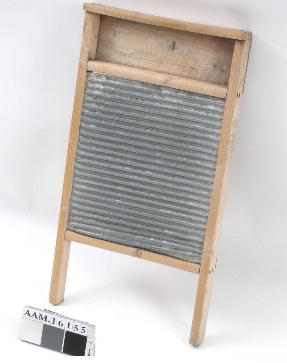 Vaskebrett,  av tre. Umalt, sinkbrett.   Forsiden har en bølget sinkplate i ramme,  som i øvre del har l hylle for sepe.