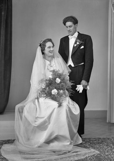53659a6353c5 Bruden är klädd i vit brudklänning med slöja och myrtenlist. Han bär frack.