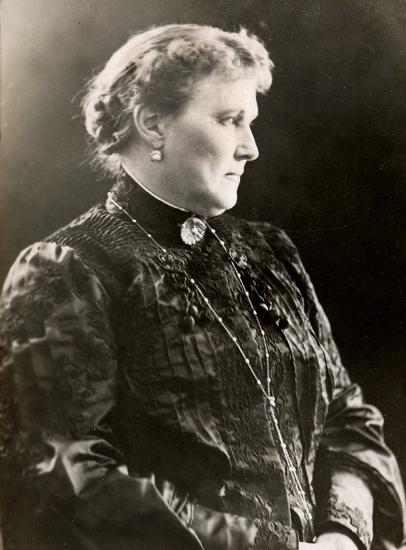 Porträttfoto av Christina Nilsson. Hon bär klänning, samt har halsband, brosch och örhänge.