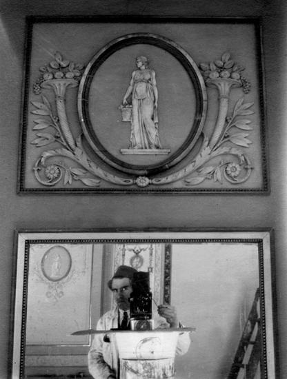 """Foto på en vägg  med spegel.I spegeln ser man fotografen. Foto från Bernshammars herrgård, Skinnskattebergs kommun, Västmanland.Herrgårdens restaurerades till stora delar på 1920-talet. (AB).Källa: Groth, Håkan, """"Neoclassicism in the North"""" (1990),s. 120-127."""