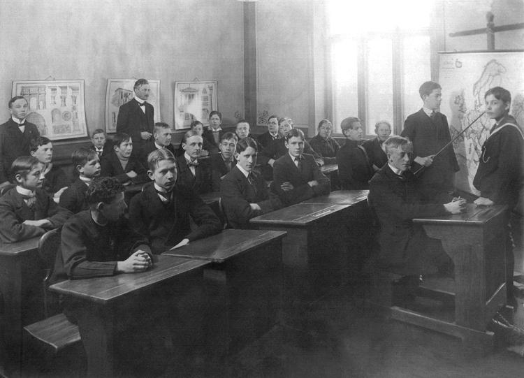 """En klass med tonårspojkar har lektion i geografi (?).Två av eleverna står framme vid en karta, som en av dempekar ut något på. I bakgrunden stpr klassens lärare, framförnågra planscher med antika arkitekturdelar.Läraren - möjl. Otto Albin Petterson (1881-1971), adjunkt v. Växjö läroverk i geografi och biologi 1911-1947 Källor: """"Lärare och Studenter vid Växjö Högre Allmänna Läroverk 1850-1950"""", (Växjö 1951), s. 36. Sveriges Dödbok 1947-2003."""