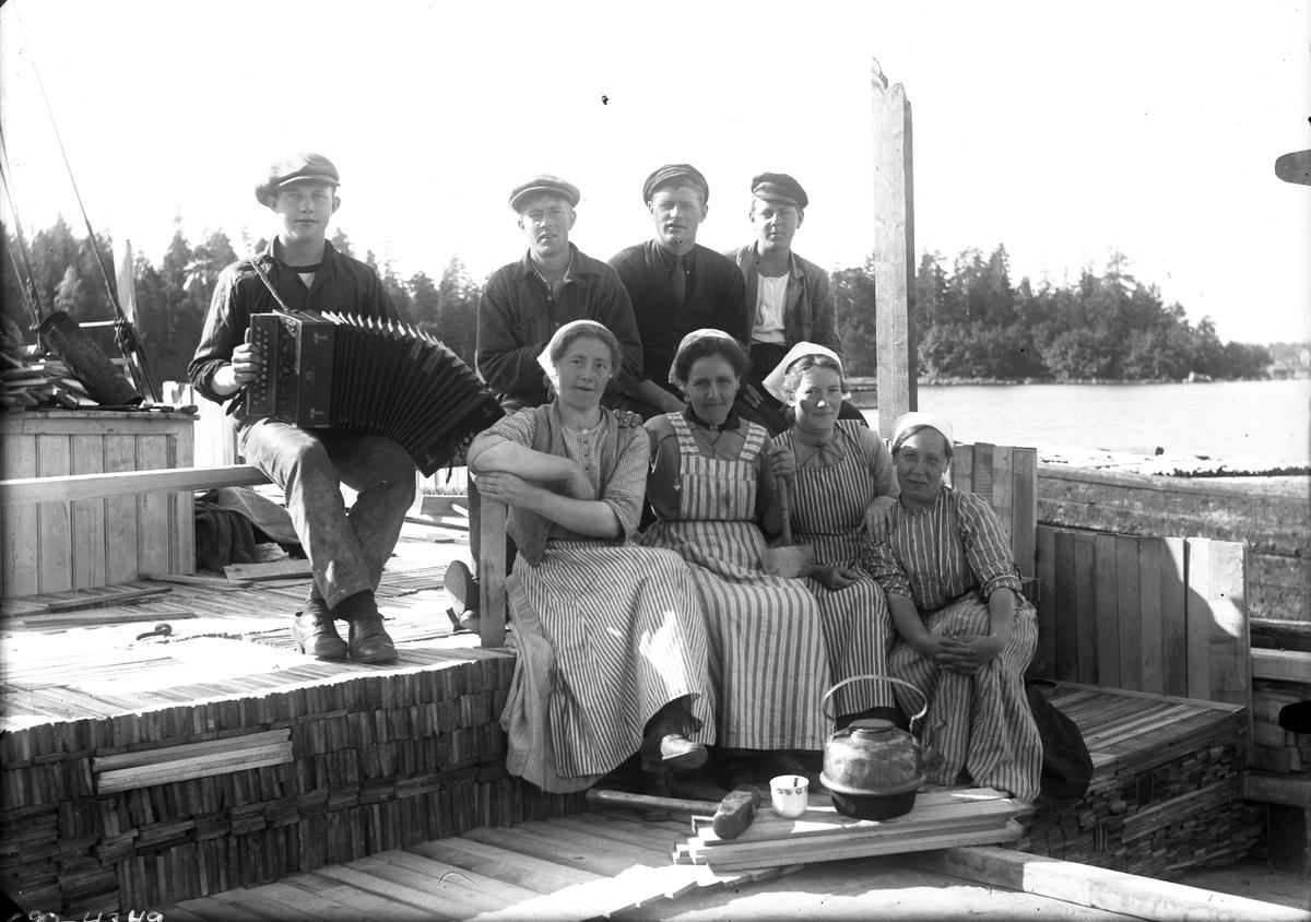 Åtta personer på en båt, en spelar dragspel.