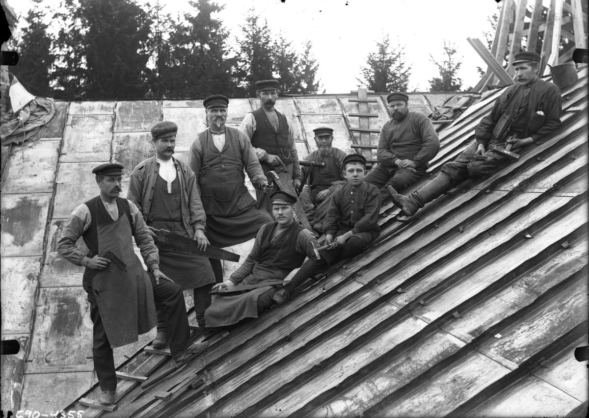 Nio byggnadsarbetare på tak.