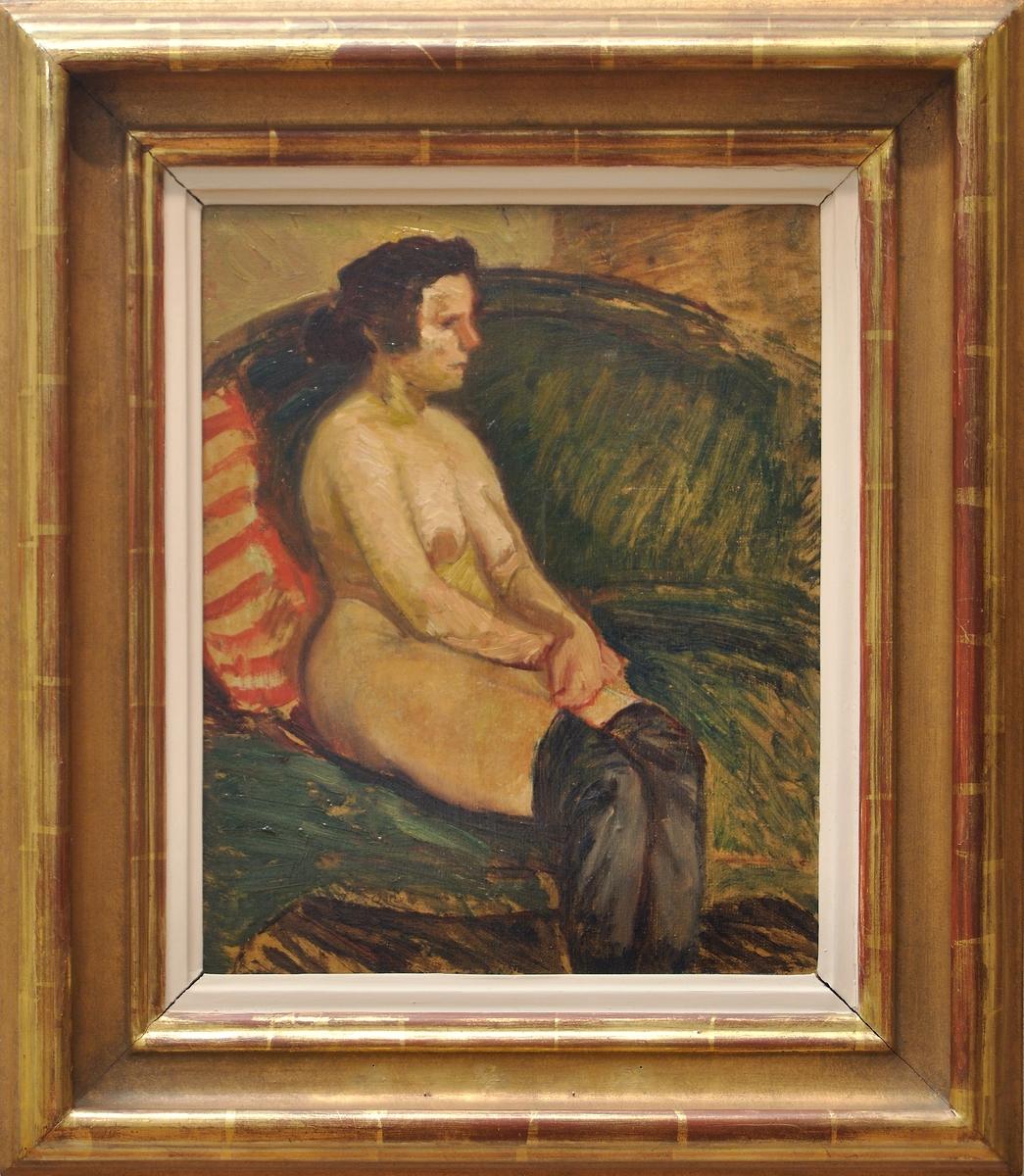 """Oljemålning på duk, """"Modellen"""" av Helmer Osslund. Naken kvinna iklädd endast svarta strumpor sittande i en grön soffa, fas något t.v. Mörkbrunt hår med knut i nacken. T.v. en rödrandig kudde. (Kat.kort) Montering/Ram: Förgylld originalram, vitmålad innerlist"""