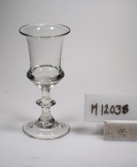 Glas. Beskrivning: Ben med knapp. Färg: Ofärgat klarglas. Mått: Diameter ovan avser glasets fotdiameter. Inskrivet i huvudkatalogen 1942.  Kataloger: Förekommer i Kostas kurant från 1855, men det är osäkert om det är samma modell. Funktion: Servisglas