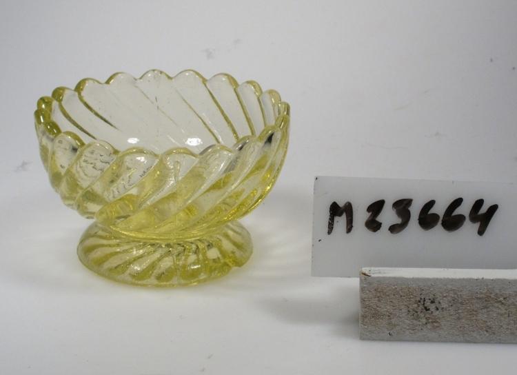 """Sockerskål """"Turbin"""". Troligen tillverkad vid Pukebergs glasbruk. Turbinmodellen tillverkades vid flera svenska glasbruk. Se även kataloger nedan. Beskrivning: Uddig kant. Vid kupa med snedställda räfflor. Inget ben. Fot med en virvel av räfflor under. Färg: Skarpt gulgrönt glas, något blåsigt. Teknik: Pressat, spår efter anhäftning. Mått: Diameter ovan avser skålens övre diameter. Fotdiameter: 44 mm. Inskrivet i huvudkatalogen 1976.  Kataloger: Pukeberg N:o 101, januari 1931. 1943 års katalog. Funktion: Sockerskål"""