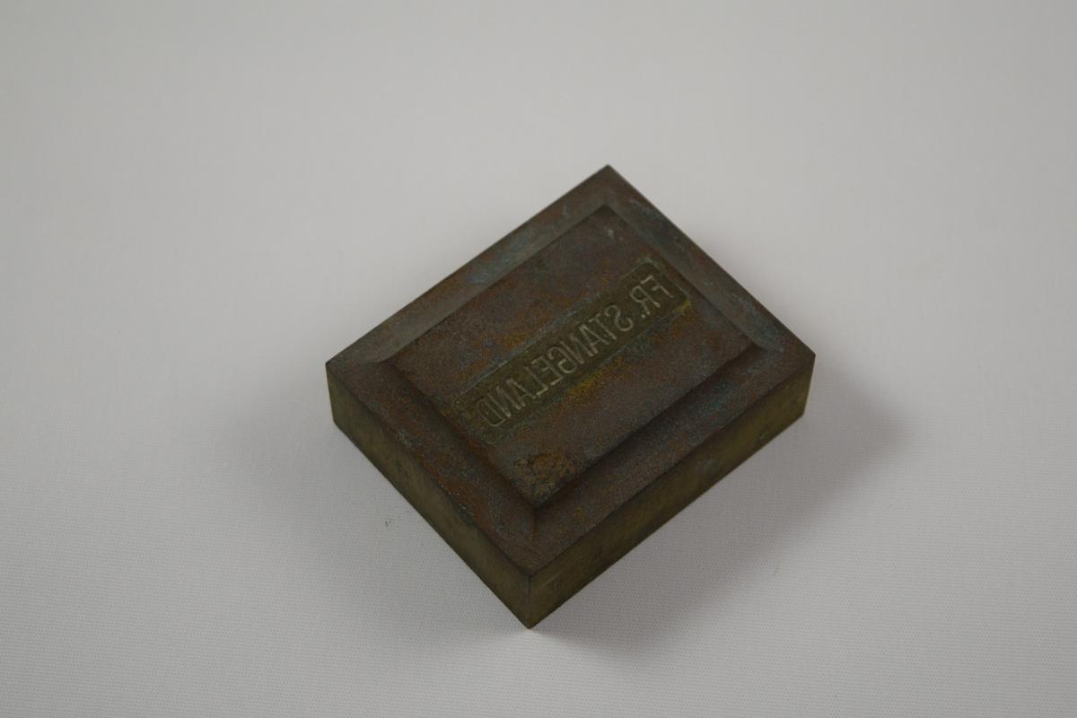 Rektangulær såpeform/stempel for produksjon av såper ved Saanums Sepefabrikk i Mandal. Kun topp. Sannsynligvis jern med messing utenpå. Opphøyd felt med inngraverte bokstaver.