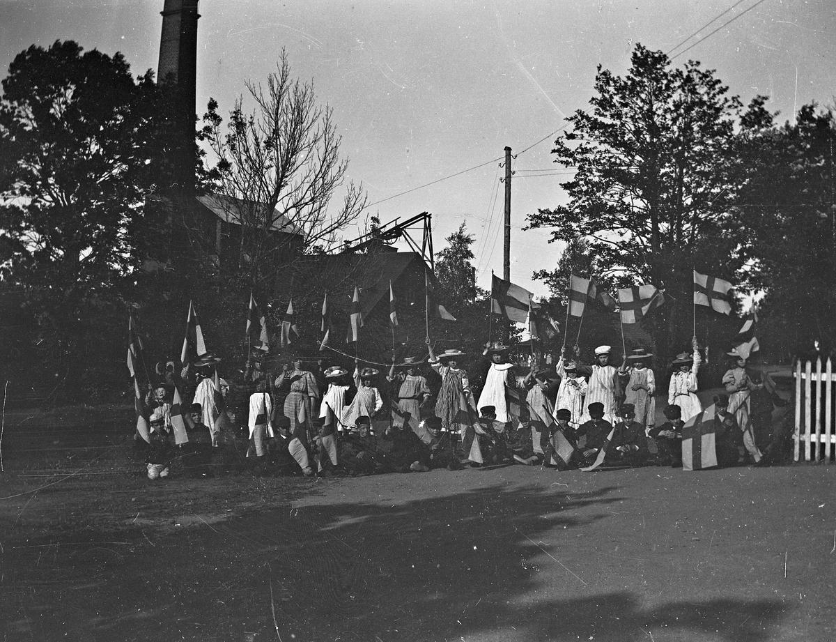Barn med flaggor vid Gammelstilla bruk, Torsåker, före 1915.