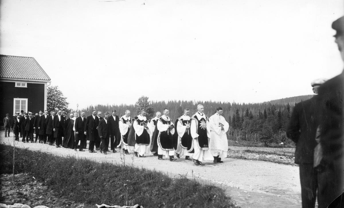 Från invigningen av Gruvbergets kapell den 4 juli 1927. Präster och kyrkvärdar på väg till invigningen av kapellet i Gruvberget. Den ljuse till vänster i första ledet är pastor Härdelin från Bollnäs, till höger i andra paret går komminister Lennart Tillgren från Bollnäs. Mitt bland kyrkvärdarna går ärkebiskop Nathan Söderblom med sin biskopsstav.