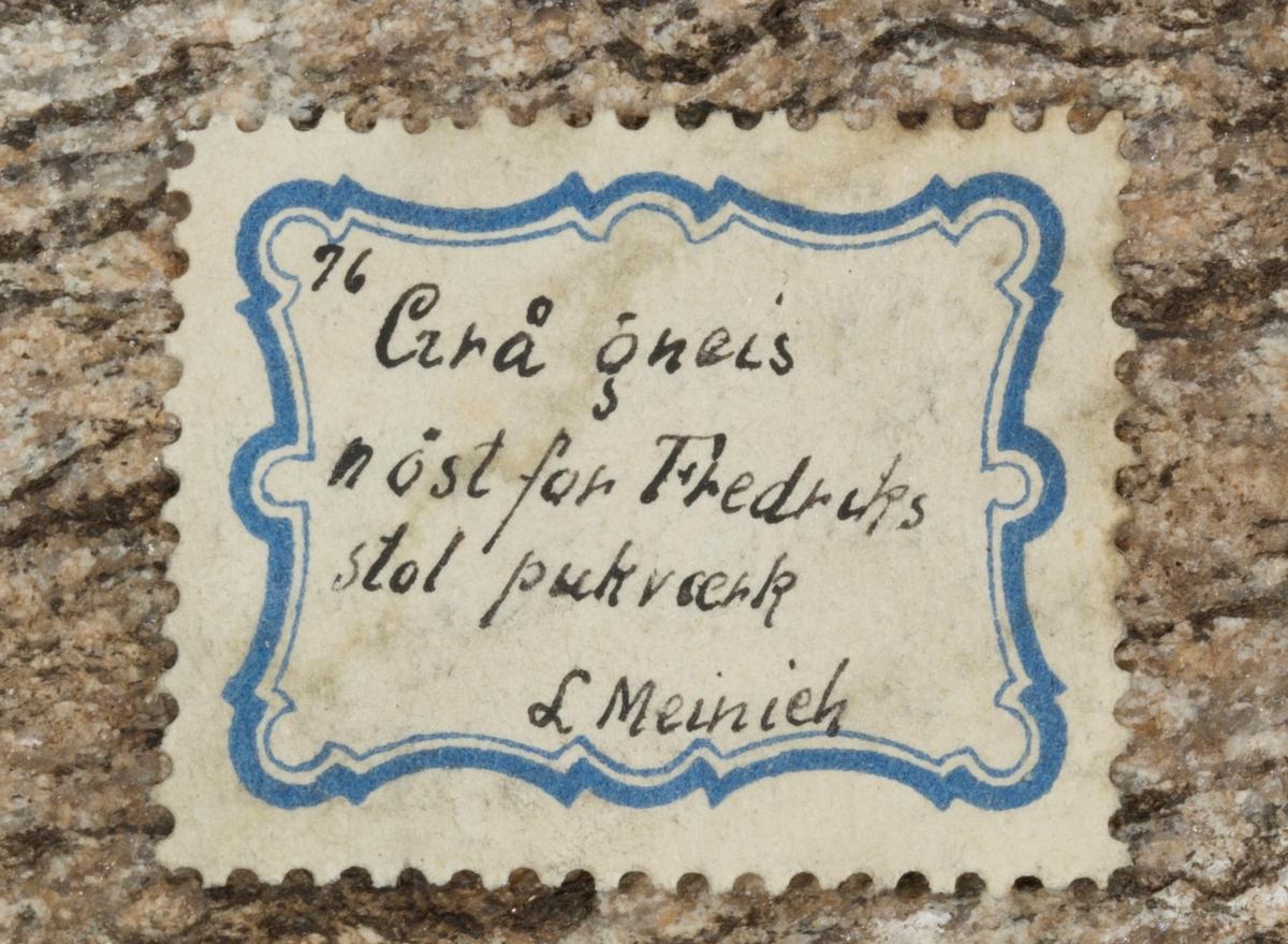 To etiketter på prøve: Etikett 1: 76 Etikett 2: 76. Grå gneis n øst for Fredriks stol pukværk. L Meinich  Etikett i eske: Kongsberg (Har stått i mineralsalen sammen med sølvstuffer)