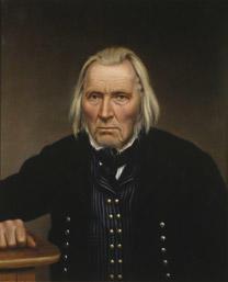 Portrett av Omund B. Birkeland. Mørk drakt med stripet vest, hvit skjorte og svart halsbind. Hviler høgre hånd på et bord.
