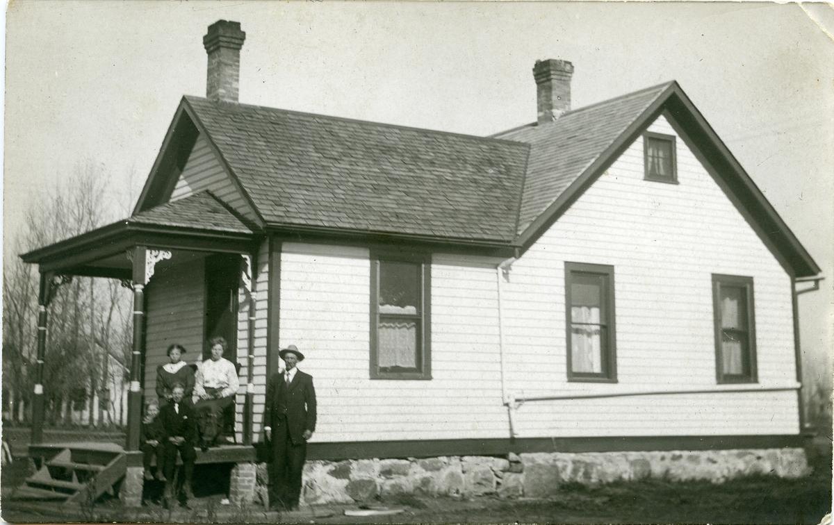En familie avbildet på trappa utenfor farm-huset sitt.