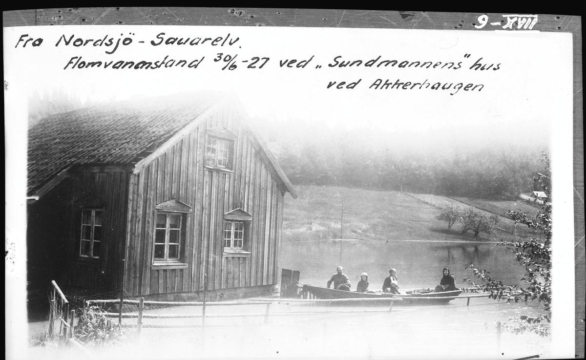 Skienselv. Sauarelv. Bildet er tatt ved Akkerhaugen jernbanestasjon og viser vannstanden i Nordsjø under storflommen i 1927. Det er ferjemannens stue som sees på fotografiet og i båten sitter ferjemannen med familie. (Arkiv: Hydrologisk avdeling, UNV_N - XVII-009)
