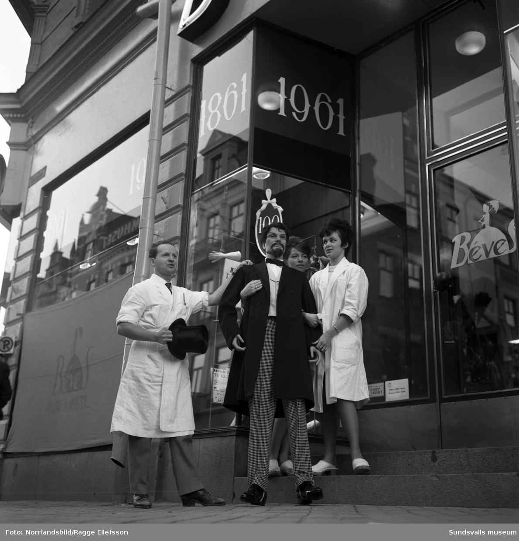 Dekorationspersonalen på Béves ekiperar och bär ut en gammal skyltdocka med anledning av firmans 100-årsjubileum.