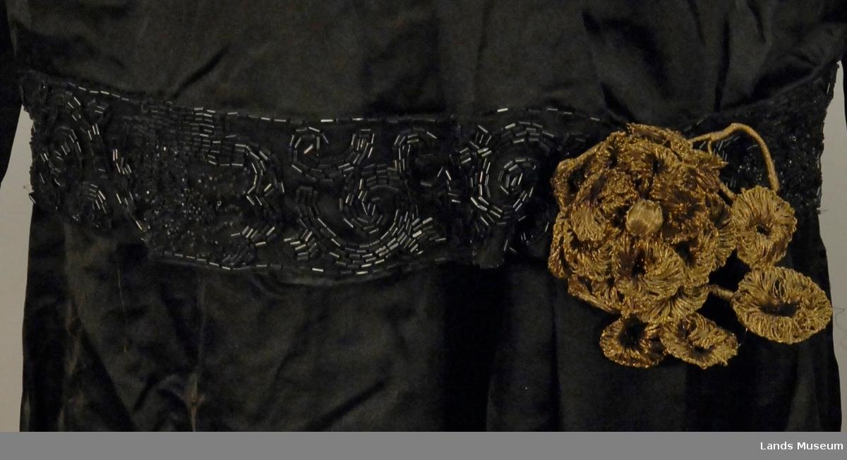 Helforet kjole med lange ermer. Kvit bomullsknipling på kvit natursilke krage som besettning i halsen. Perlebroderi i svart på svart tyll, festet på skjerf og linning i livet. Skjerfet har også perlefrynser. Pynteblomst i metall i livet. Fotsid kjole med slep.