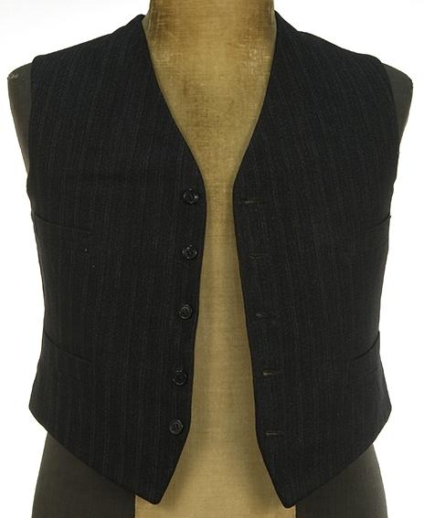 Stripet vest med knapping foran silkefor. Spensel i ryggen 4 skråstilte lommer