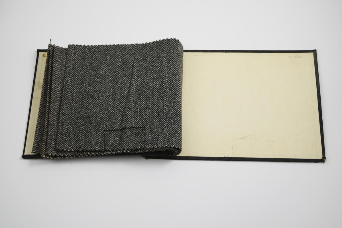 """Prøvebok med 4 prøver. Middels tykke stoff med diskret fiskebensmønster - mønsteret er likt på forsiden og baksiden av stoffet. Stoffene ligger brettet dobbelt i boken. Stoffene er merket med en rund papirlapp, festet til stoffet med metallstifter, hvor nummer er påført for hånd. Innskriften på innsiden av omslaget indikerer at alle stoffene har kvaliteten """"Olav"""".   Stoff nr.: Olav/4, Olav/8, Olav/15, Olav/16."""