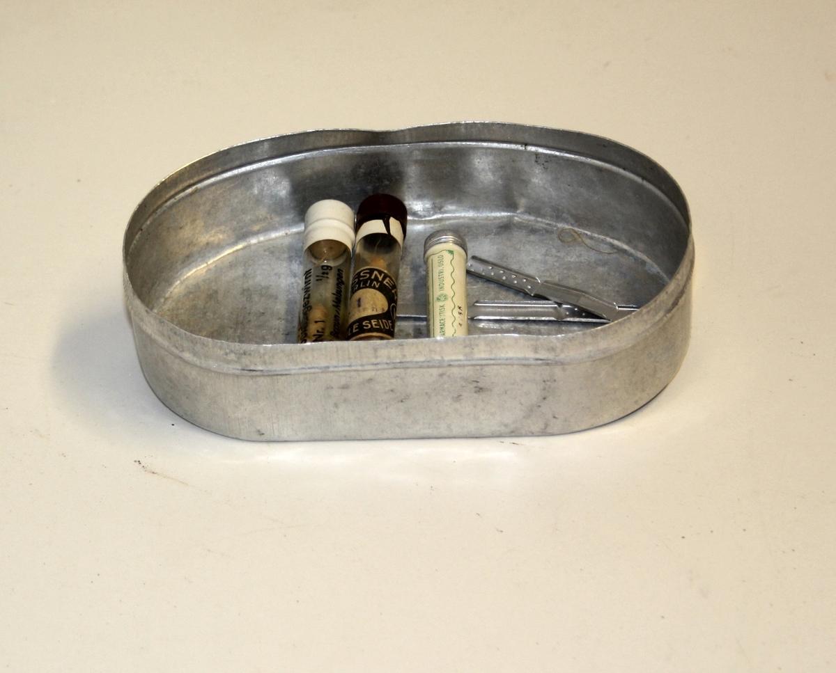 """Oval aluminiumsboks med innhold. Innhold er plastslange, 2x tråd, 2x klemmer til til navlestreng, glass sylinder, 2x beholdere med medisin (Sol. nitr. arg. og Nervinal """"afi"""")."""