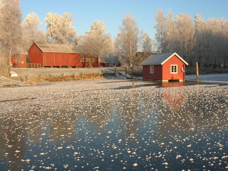 Foto av hvilebrakke og båthus om vinteren