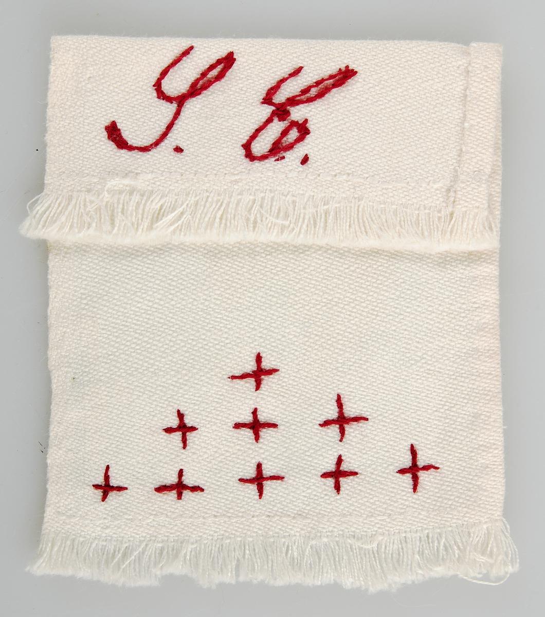 Långsmalt hänge eller paradhandduk i vitt linne med rött broderi.
