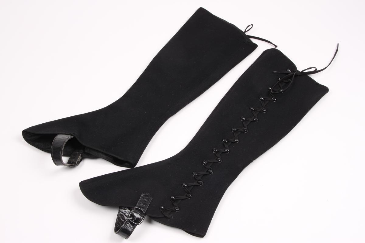 Et par gamasjer i svart ullblanding med silkefôr.  Gamasjene lukkes med lisser gjennom kroker og maljer langs fotens innside. Gamasjene har lærremmer med metallspenne til å feste under foten.
