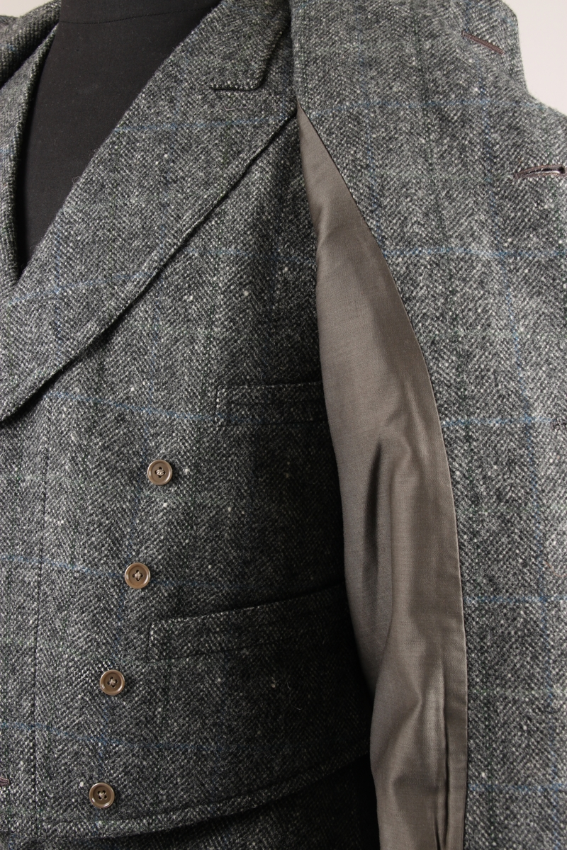 Jakke med tre knapper og fire lommer på fronten. Det er tre knapper på hver jakkeerme. Jakken er fôret med et mørkegrønt stoff og det er en innerlomme på høyre side.