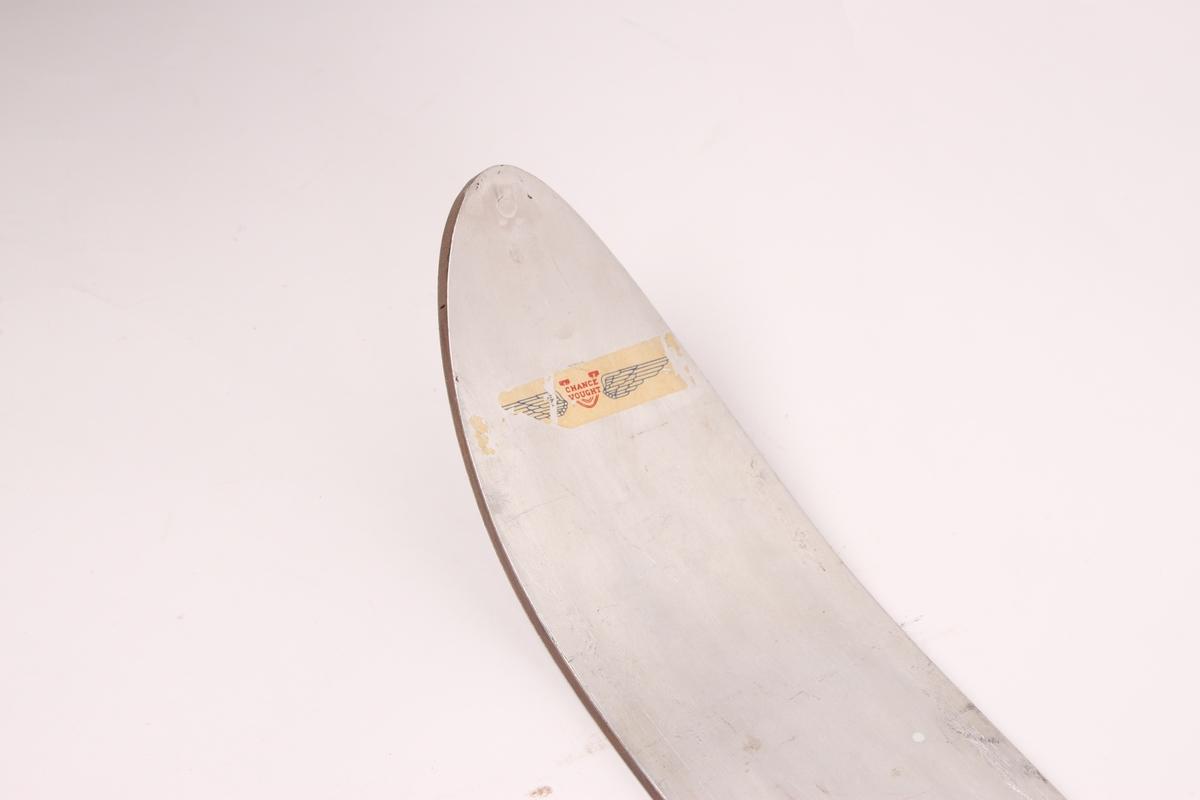 Ski i tre og magnesium. Skiene har en enkel tupp med fortykning og et aluminiumsbelegg på oversiden av skien både foran og bak.