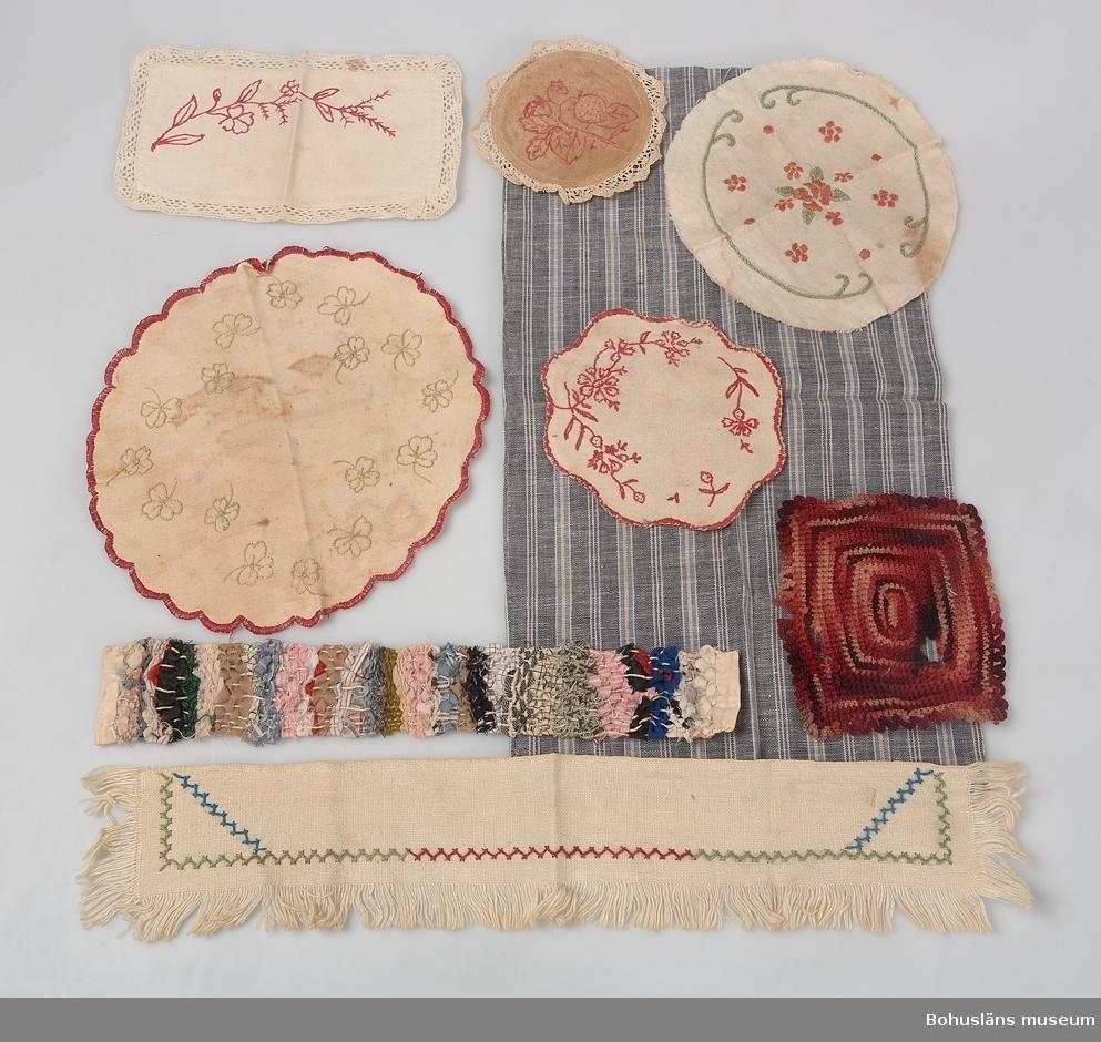 """Grå strumpkartong med röd kant på locket. Påklistrad etikett: """"Handelsmärke Regina, lila"""" """"No S17081/4 St 9, 91/2. 2:--"""". Resväska i brun papp innehåller 25 mössor i olika färger och modeller. En grön kartong innehåller mössor, och blusar. Byxdress 4st, kappa 1st, klän- ningar 19 st, förkläde 1 st, byxor 10 st, haklapp 1 st, kjolar 5st, skor 8 st, koftor 7 st. Sidenband: 1 blått, 1 rött o 2 skära. Svart sammetshalsduk med röda fransar, trasmatta 1st, dukar 7st samt en grårandig tygpåse. Ett kuvert med mönster till dockkläder."""