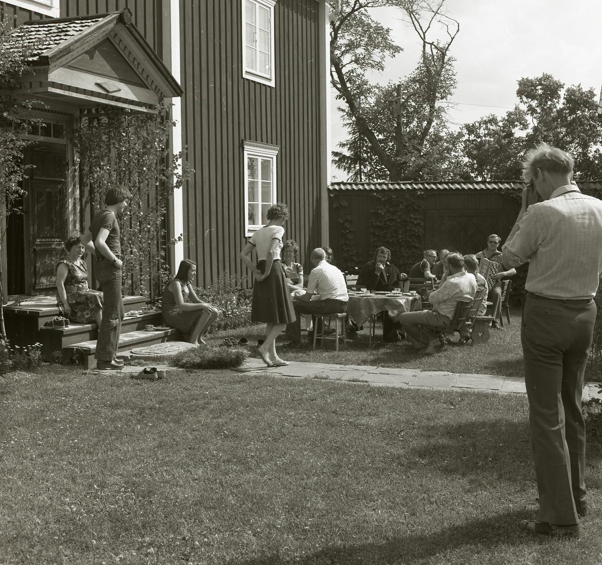 I trädgårdsmöblerna på gården Sunnanåker är ett sällskap bänkade för en kaffetår midsommarafton 1978. Intill husväggen har gruppen funnit en solig plats för avkoppling och underhållning då en av männen spelar dragspel.
