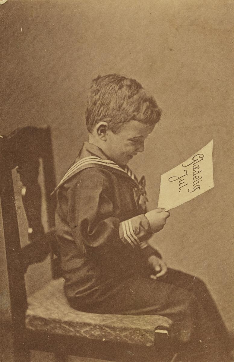 Julekort. Jule-og nyttårshilsen. Gutt i matrosdrdss, som sitter på en stol med en julehilsen. Sorthvit bilde.