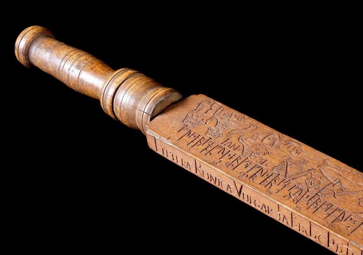 Kalenderstav i form av en svärdsfomad runkalender. Av trä, med en rektangulär genomskärning och svarvat handtag. På de breda sidorna finns själva kalendern inskuren med runor och symboler. På en av de smala sidorna finns texten: Littera Runica Vulgar och därefter en omvandlingstabell för runor till arabiska bokstäver och siffror. På den andra smala sidan diverse latinsk text samt namnet på tillverkaren. Se Historik. Mått: utan handtag 120,3 cm lång.