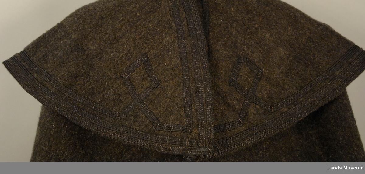 Lang kappe i svart, med svart og kvitt rutemønster på innsida. Stor rundt krage.