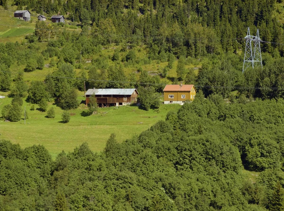 Fonstadbakken. Gulbrunt bolighus og rødbrunt uthus. Litt dyrka mark, mye skog og utmark rundt.