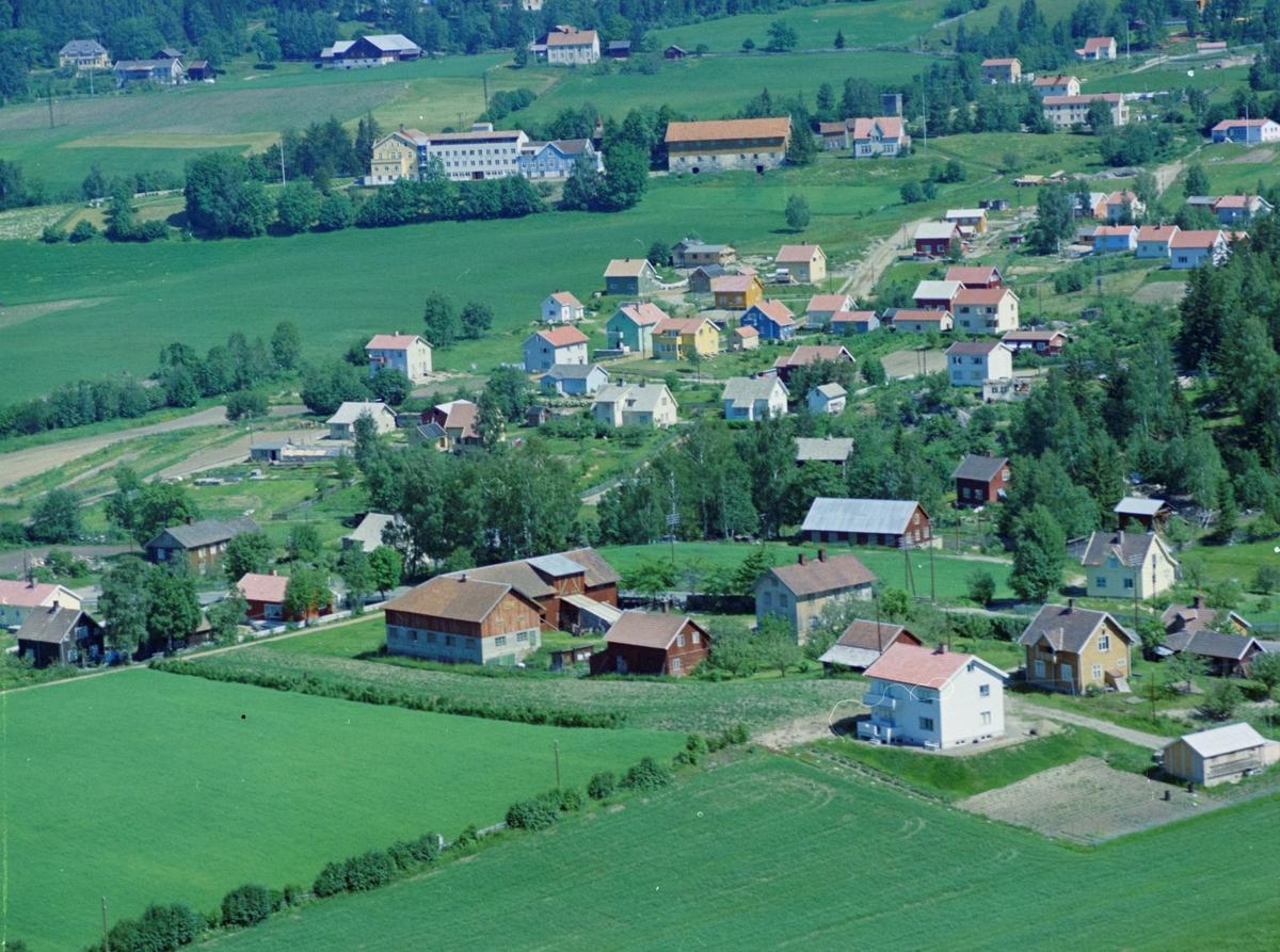 """Flyfoto, Lillehammer, Søre Ål.  Oversiktsbilde med Kolsveen (Kullsveen) gård midt i bildet, Hamarvegen 124. Det hvite huset nærmest er Hamarvegen 126. I høyre bildekant ligger ungdomshuset """"Solheim"""". Øverst ligger Holen gård og Skogli sanatorium. Den nye vegen oppover midt i bildet er Hagehaugvegen."""
