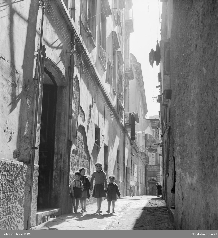 Fyra barn som kommer gående på en smal gata
