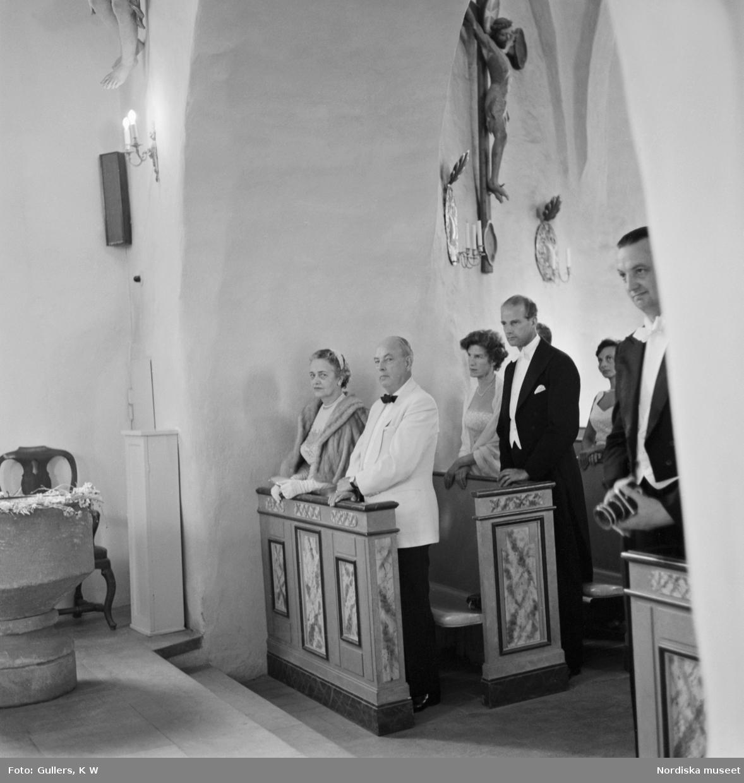 Högtidsklädda människor som ståt uppställda i en kyrka.