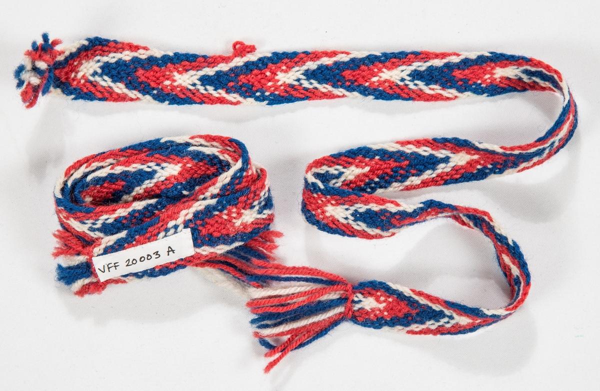Sokkebanda er fletta i raudt, blått og kvitt ullgarn.