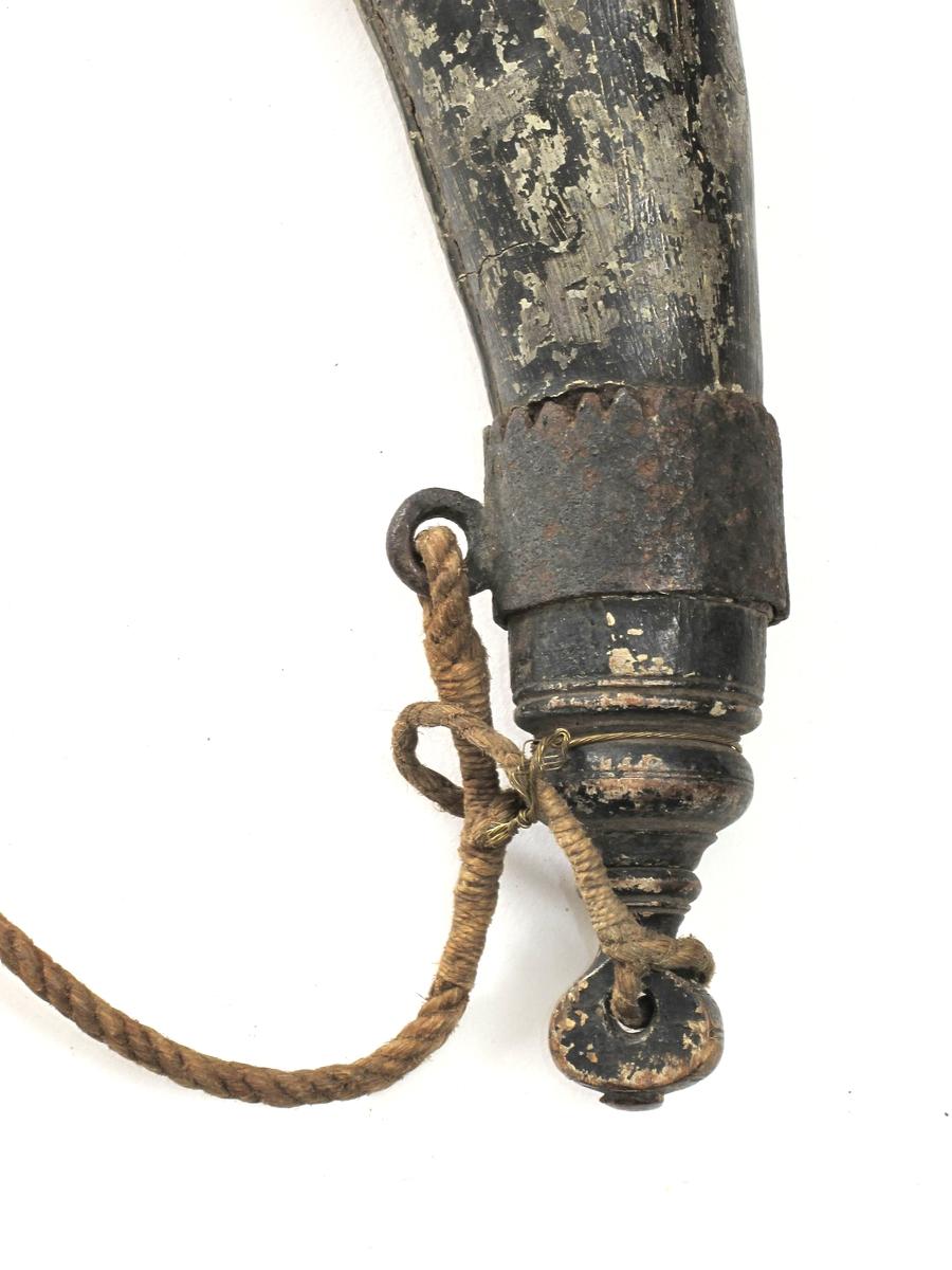 Krutthorn, imitert horn av malt tre,  med sortmalt trelokk og bunn, jernbeslag og   messingknapper. Horn malt i hornimitasjon med lysbrune striper, sort i nedre del.  Skjøt langs innsiden av buen. Sort  dreiet  lokk med nedsenket toppflate, stor dreiet knott med skrugjenger.  Under trelokket to rader med messingknapper. I nedre del et jernbeslag med takker langs overkanten, i dette en jernring  for feste av bæresnoren av tau.