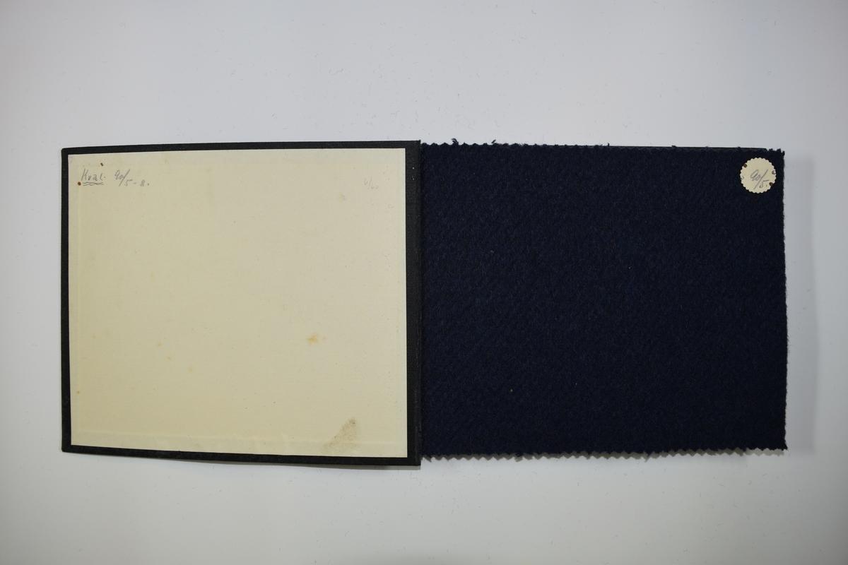 Prøvebok med 4 stoffprøver. Tykke ensfargede stoff. Bare fargen varierer mellom prøvene i boken. Stoffene ligger brettet dobbelt slik at vranga dekkes. Stoffene er merket med en rund papirlapp, festet til stoffet med metallstift, hvor nummer er påført for hånd.   Stoff nr.: 90/5, 90/6, 90/7, 90/8.