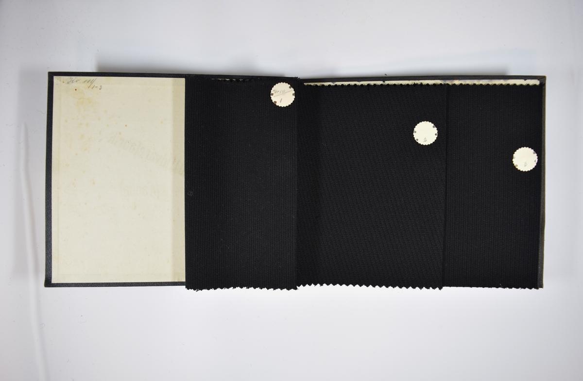 Prøvebok med 3 stoffprøver. Middels tykke ensfargede sorte stoff med diskret striper av ulike slag. Stoffene ligger brettet dobbelt i boken slik at vranga dekkes. Stoffene er merket med en rund papirlapp, festet til stoffet med metallstift, hvor nummer er påført for hånd. Innskriften på innsiden av forsideomslaget indikerer at alle stoffene har kvalitetsnummer 111.   Stoff nr.: 111/1, 111/2, 111/3.