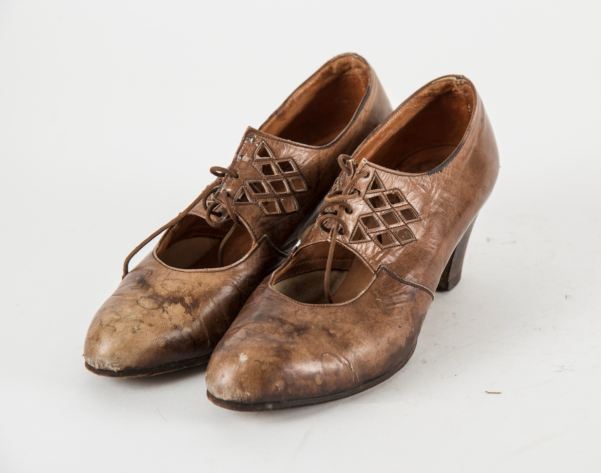 Sko, A og B i brunt skinn. Gjennombrutt mønster på overleret. Snøresko med fire par hol, tynn skolisse. Høg hæl.