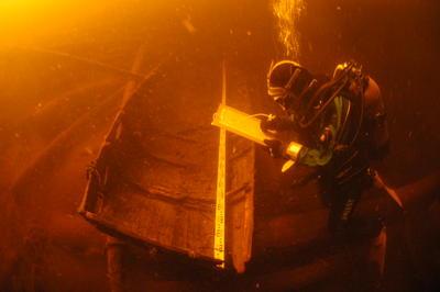 Rester av en båt på sjøbunnen, foran en dykker som skriver på ei notatblokk.
