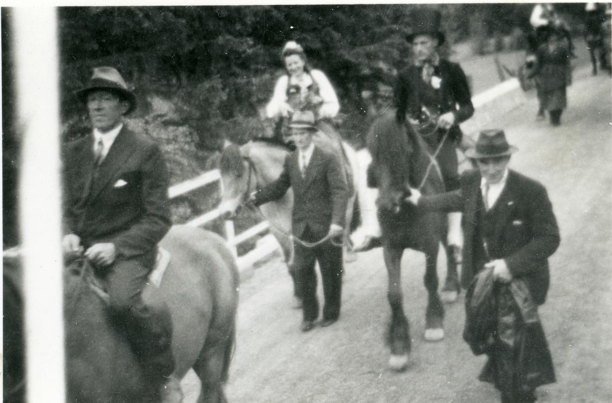 Brudefølge på Bagn Bygdesamling. Nikolai Bøhle leier hesten til brura.