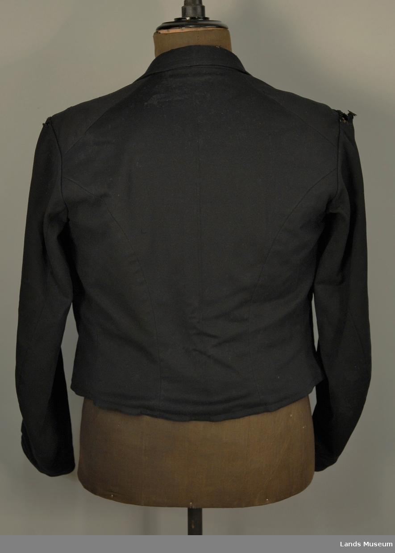 A: Trøya er sydd av meget fint klede eller en drapé. Maskinvevd og -sydd. Håndsøm, skreddersøm. Skuldersøm skrått mot rygg, midtsøm, panelsømmer, litt skrådd sidesømmer, snittsøm fra nederkant 18 cm opp. Dobbeltspent, skrådd, tre knapphull i hver trekant, fem metallkuleknapper med dekor. Slag, nedbrettet krage, stikklomme på rette og vrange av venstre side. Tosømserme, glatt isydd bomullsfôr, lerret i ermene, 4 skaftet kypertvev i bolen.  B: Vest i sørt klede med lerretsrygg. 10 knapper. Dobbeltkanppet. 3 stikklommer.