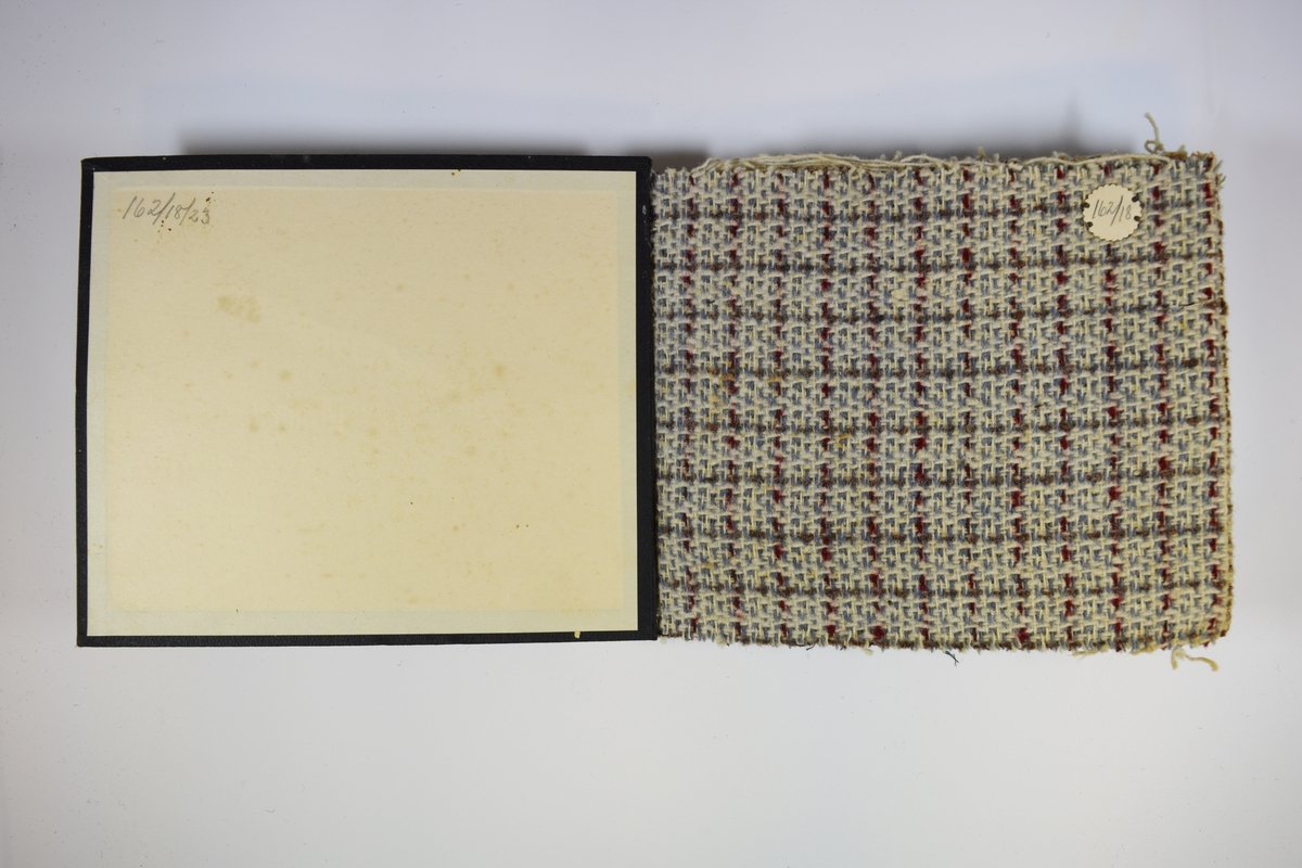 Prøvebok med 6 prøver. Middels tykke flerfargede stoff med rutemønster. Ulike farger og kombinasjoner på stoffene, men vevemønsteret er likt.  Tovet overflate. Baksiden er ikke tovet. Stoffene ligger brettet dobbelt i boken. Stoffene er merket med en rund papirlapp, festet til stoffet med metallstifter, hvor nummer er påført for hånd. Innskriften på innsiden av forsideomslaget indikerer at alle stoffene har kvaliteten 162.   Stoff nr.: 162/18, 162/19, 162/20, 162/21, 162/22, 162/23.
