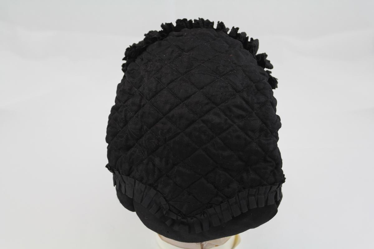 Sort silkedamask med småblomstret mønster, gråbrunt bomullsfor mønstret med hvite ovaler. Hetten har et halvsirkelformet bakstykke som ned mot nakken ender i en trekant. På sidene er festet trekantete ørestykker. Langs hettens fremkant og langs ørestykkene og bakstykkets underkant er påsatt en silkebåndrysj. Under bakstykket er et poseformet nakkeparti som nederst er rynket sammen med trekkbånd. Taftbånd til å knytte under haken. Bakstykket og ørelappene er stukket til regelmessige romber.